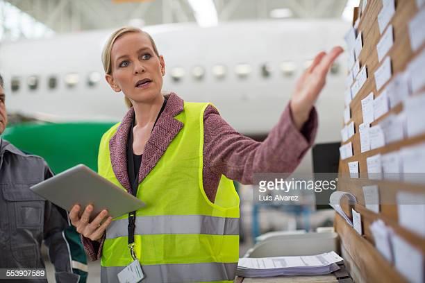 Supervisor holding digital tablet in hangar