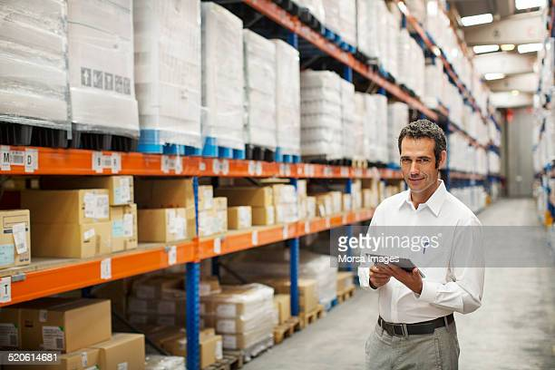 Supervisor holding digital tablet in warehouse