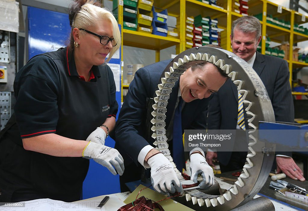 Supervisor Jane Paley looks on as Conservative Chancellor George Osborne works on part of a generator during a visit to Winder Power on May 5, 2015 in Pudsey, England. The British public go to the polls in the general election on May 7th.