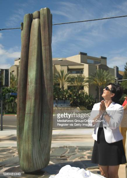 Supervisor Lisa Bartlett gazes at artist Richard Turner's bronze sculpture of a 7foottall celery stalk after the unveiling at the new Flower Street...