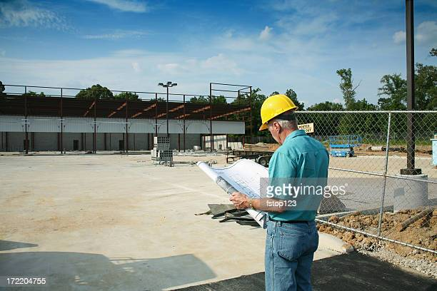Supervisor man wearing hardhat and holding blueprints at construction site.