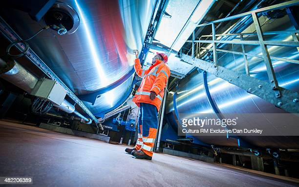 Supervisor monitoring new machinery at industrial plant