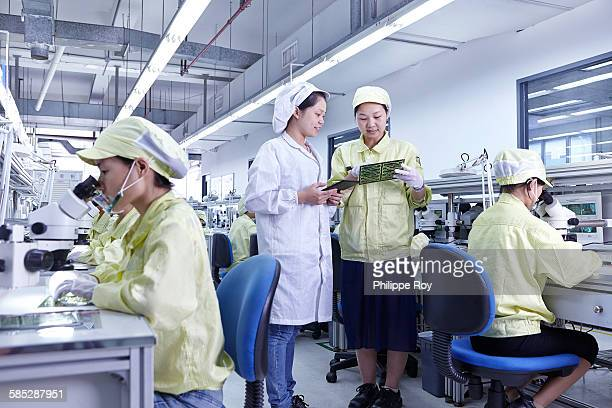 Supervisor overseeing work at quality check station at factory producing flexible electronic circuit boards. Plant is located in the south of China, in Zhuhai, Guangdong province
