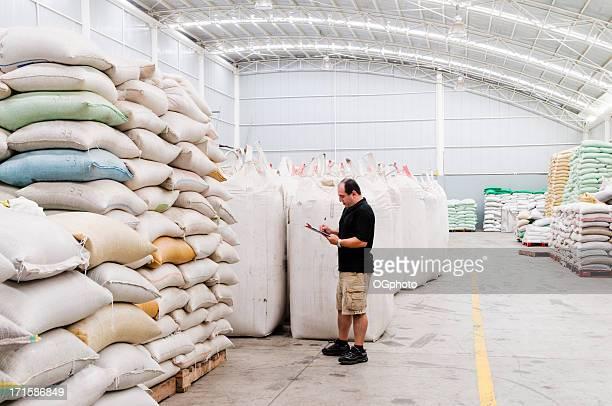 supervisor taking inventory of merchandise in a modern warehouse - ogphoto stockfoto's en -beelden