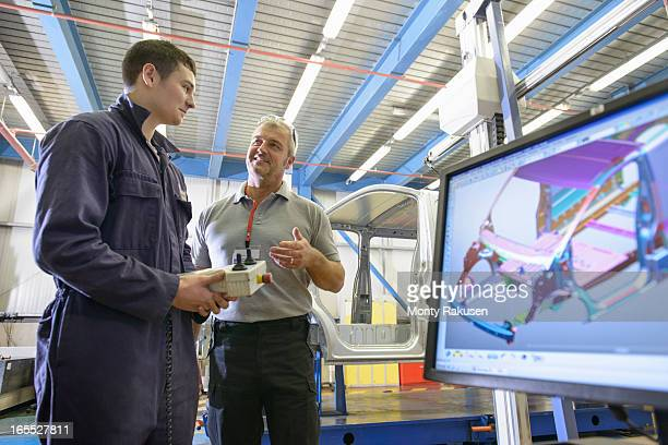 Supervisor teaching apprentice wearing boiler suit in car plant.  Computer image of car body on monitor in foreground