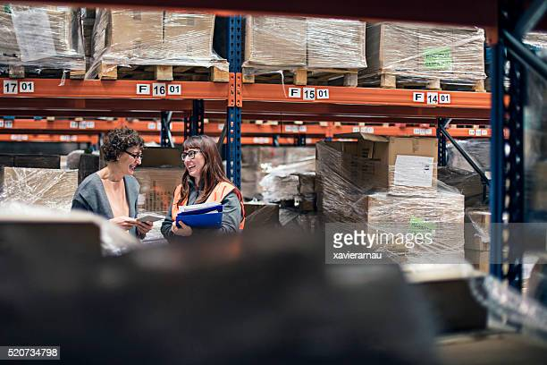Supervisor woman with digital tablet in warehouse talking to worker