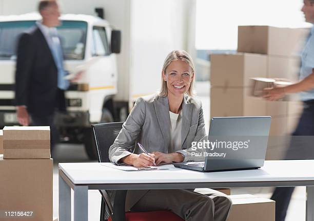 Supervisor working on laptop in shipping area