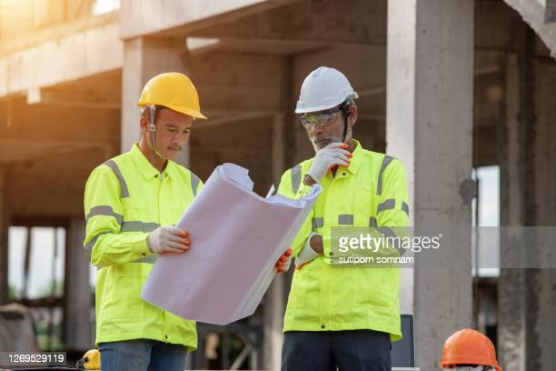 supervisors engineering reading blueprint at the construction site - 578105427 stock pictures, royalty-free photos & images