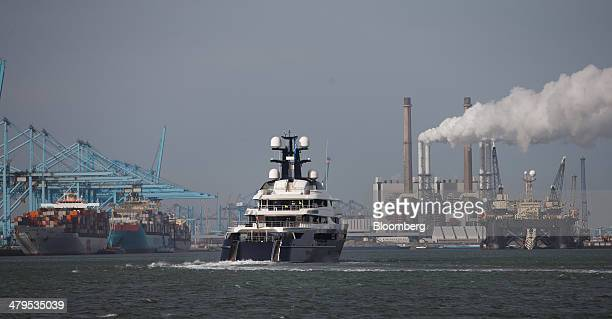 A superyacht constructed by Oceanco undergoes seatrials as ship to shore cranes and chimney stacks stand beyond on the shoreline in Rotterdam...