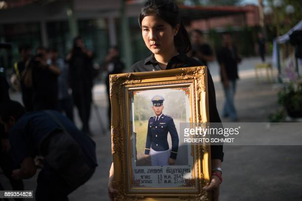 Supicha Tanyakan the sister of Pakapong Tanyakan a first year cadet in the Thai army carries his photo during a cremation ceremony in Chonburi on...
