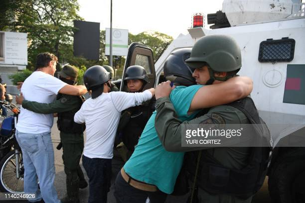 Supoprters of self-proclaimed acting president Juan Guaido hug members of the security forces in Caracas on April 30, 2019. - Venezuelan opposition...
