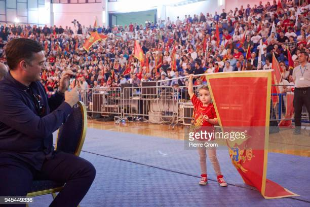 A suporter of Milo Dukanovic the presidential candidate for the ruling party Democratic Party of Socialists of Montenegro takes a photo of a child...