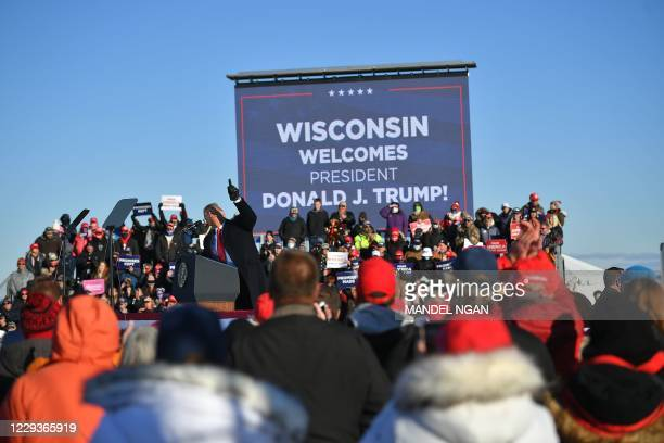 Suporters listen to US President Donald Trump speak during a campaign rally at Green Bay Austin Straubel International Airport in Green Bay,...