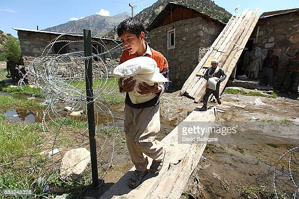 Supplied by the US Army's 10th Mountain Division local villagers collect humanitarian aid from the District Center at Barge Matal Nuristan province