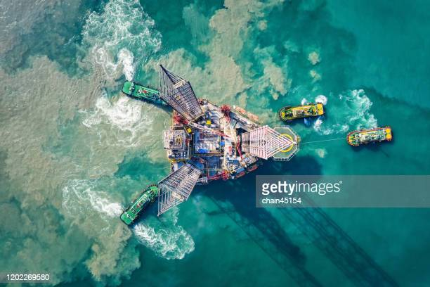 supply boat are towing oil drilling rig for transportation to oil field platform for oil and gas business. - oil industry stock pictures, royalty-free photos & images