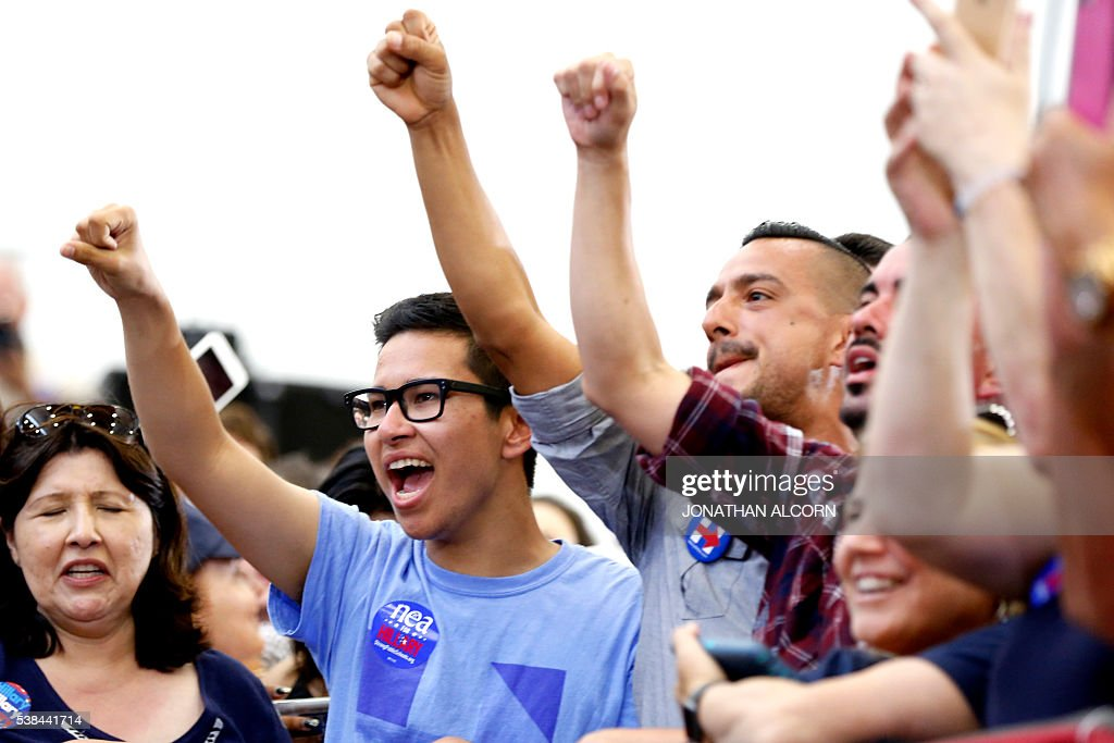 Suppoerters of Democratic presidential candidate Hillary Clinton cheer during a rally at Long Beach City College on the final day of California campaigning, June 6, 2016 in Long Beach, California. Hillary Clinton has received commitments from enough delegates to clinch the Democratic presidential nomination, according to the Associated Press and US networks, ensuring she will be the first woman to lead a major US party in the race for the White House. / AFP / JONATHAN