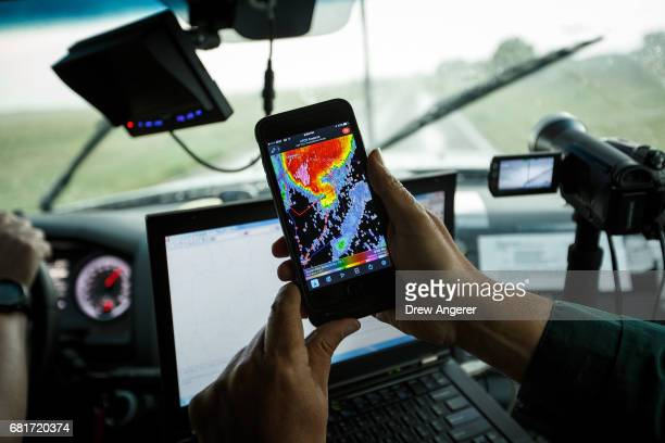 Support scientist Tim Marshall a 40 year veteran of storm chasing looks at radar on his smartphone as the group tracks a supercell thunderstorm May...