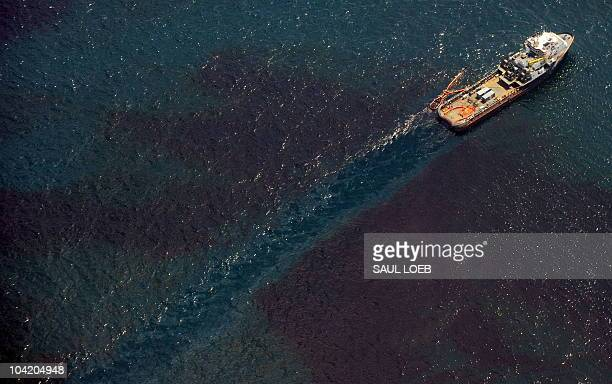 A support ship related to the collection of oil from over the site of the BP Deepwater Horizon oil well transitions through a sheen of oil as workers...
