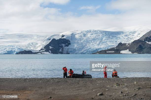 Support team for Brazilian researchers waiting on the Wanda Glacier beach in Lussich Cove with the Dobrowolski Glacier in the background, on January...