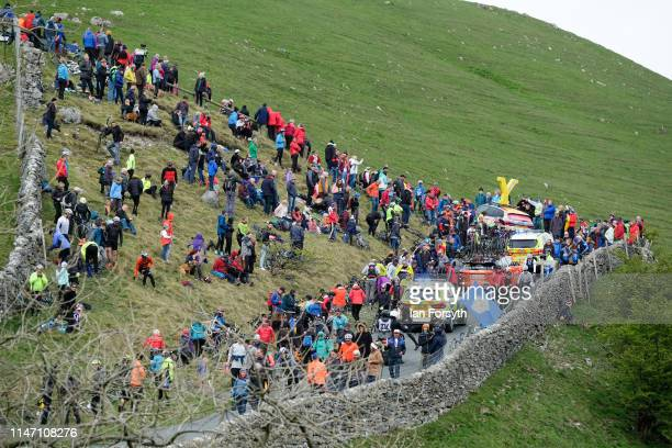 Support vehicles follow the peleton up the Cote de Park Rash ascent near the village of Kettlewell in the Yorkshire Dales during the fourth and final...