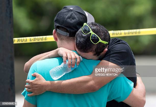 Supported by a friend a man weeps for victims of the mass shooting just a block from the scene in Orlando Florida on June 12 2016 Fifty people died...