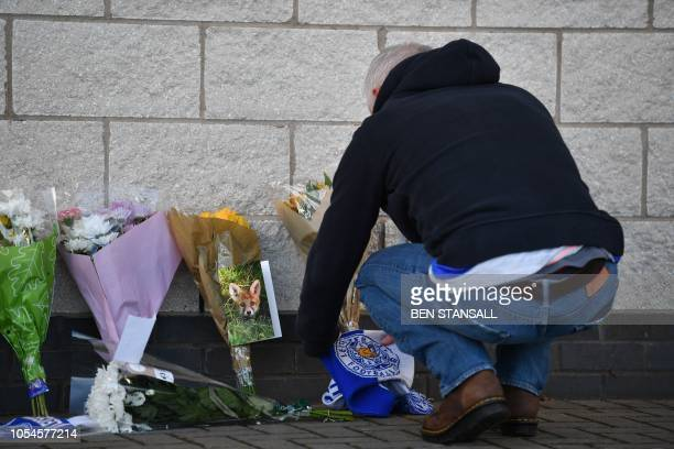 A supporter adds flowers and a Leicester City scarf to floral tributes lined up outside Leicester City Football Club's King Power Stadium in...