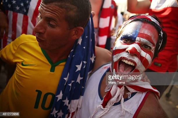 S supporter and a Brazil supporter celebrate the US advancing to the Round of 16 after their loss to Germany while watching the match at FIFA Fan...