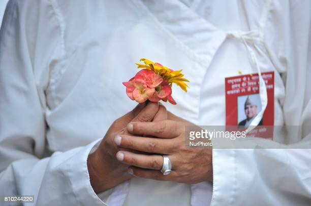 Supporter and well-wisher holds flower to offer to Former King Gyanendra Shah during on his 71th birthday at his residence Nirmal Niwas, Maharjagunj,...