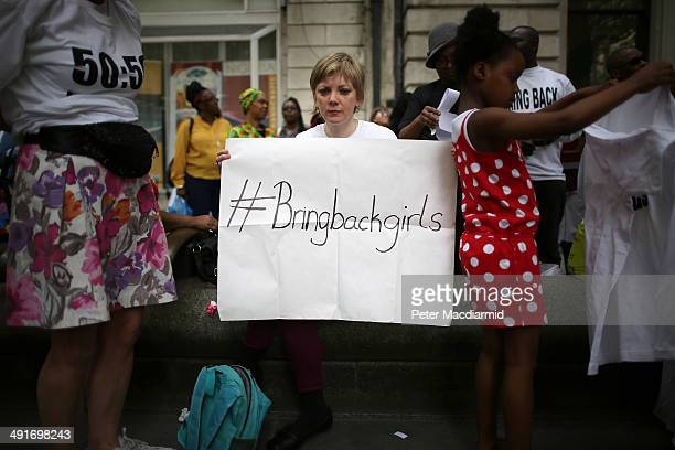A supporter calling for the release of schoolgirls abducted by Boko Haram Islamists waits for the start of a protest march at the Nigerian embassy on...