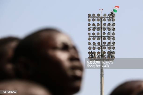 A supporter carries a People's Democratic Party flag up a light post during a campaign rally of Nigerian PDP opposition presidential candidate Atiku...