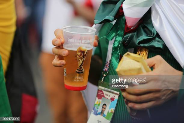 A supporter carries a plastic cup of beer outside Luzhniki Stadium ahead of the FIFA World Cup final match in Moscow Russia on Sunday July 15 2018...