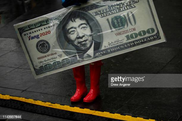 A supporter carries a sign representing Democratic presidential candidate Andrew Yang's plan for a $1000 monthly universal basic income during a...