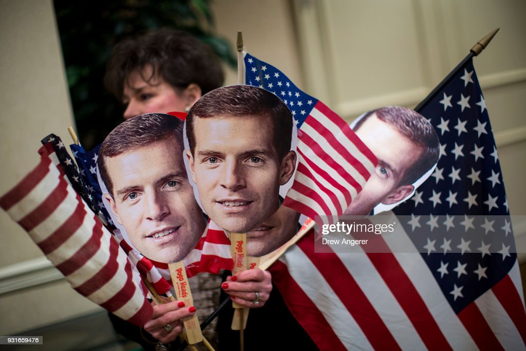A supporter carries flags and photos of Conor Lamb at an election night event for Conor Lamb, Democratic congressional candidate for Pennsylvania's 18th district, March 13, 2018 in Canonsburg, Pennsylvania. As of 10:00 PM, Lamb's race against Republican candidate Rick Saccone is still too close to call.