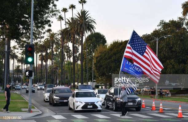 Supporter carries flags as he crosses an intersection during a rally in support of US President Donald Trump in Beverly Hills, California, October...