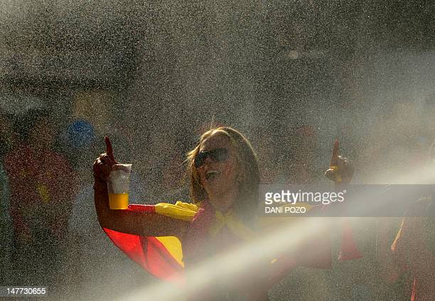 A supporter celebrates as the Spanish national football team arrives on Cibeles Square on July 2 2012 after parading through Madrid a day after it...