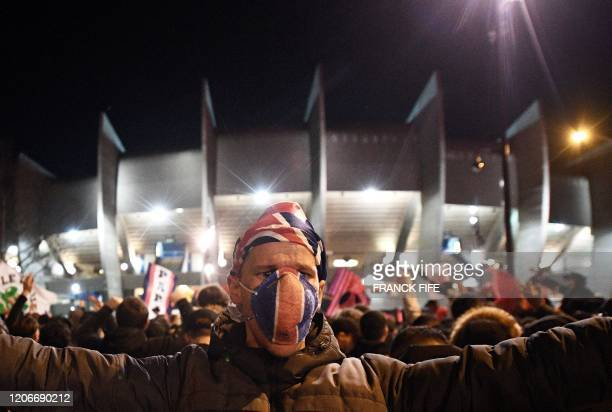 A PSG supporter celebrates outside the Parc des Princes stadium in Paris during of the UEFA Champions League round of 16 second leg football match...