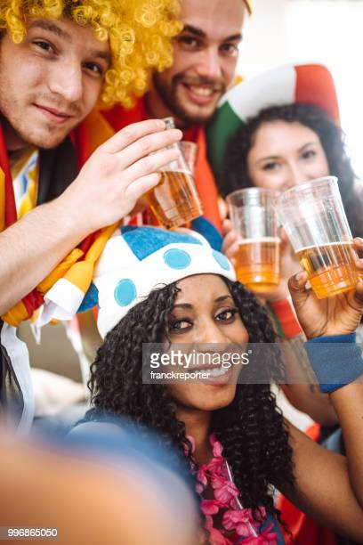 supporter cheering with beer in front of the TV
