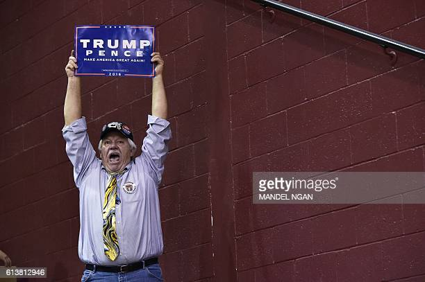 A supporter cheers as Republican presidential nominee Donald Trump speaks during a rally at Ambridge Area Senior High School on October 10 2016 in...