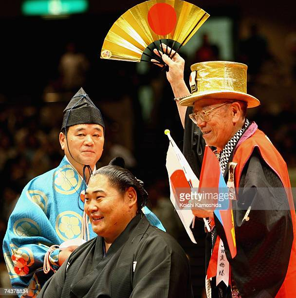 A supporter cheers sumo wrestler Kyokushuzan of Mongolia after he had his top knot cut off during Kyokushuzan's retirement ceremony at the Kokugikan...