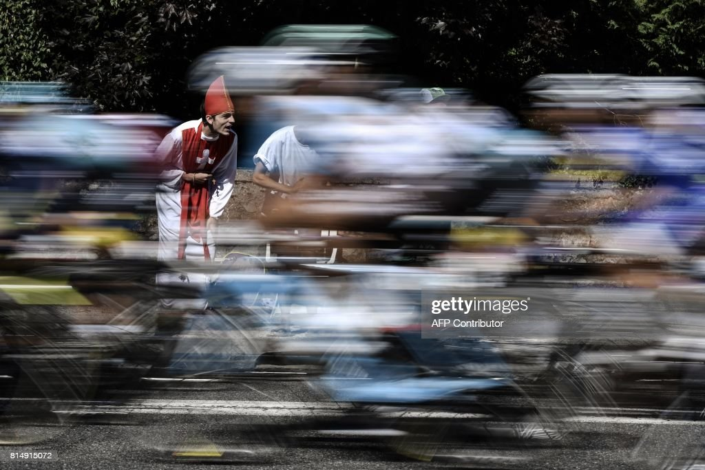 TOPSHOT - A supporter disguised as a priest cheers as the pack rides during the 181,5 km fourteenth stage of the 104th edition of the Tour de France cycling race on July 15, 2017 between Blagnac and Rodez. / AFP PHOTO / Jeff PACHOUD
