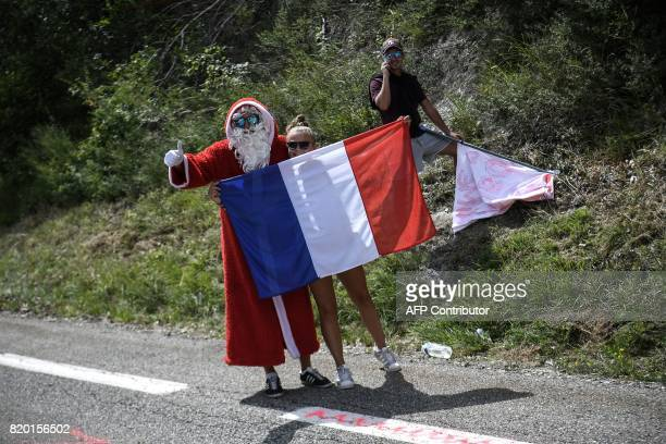 A supporter disguised as Santa Claus cheers behind a French national flag along the road during the 2225 km nineteenth stage of the 104th edition of...