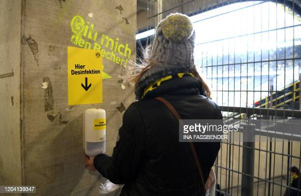 A supporter disinfects his hands upon his arrival for the German first division Bundesliga football match Borussia Dortmund v SC Freiburg on February...