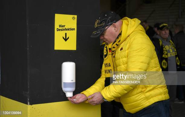 Supporter disinfects his hands upon his arrival for the German first division Bundesliga football match Borussia Dortmund v SC Freiburg on February...