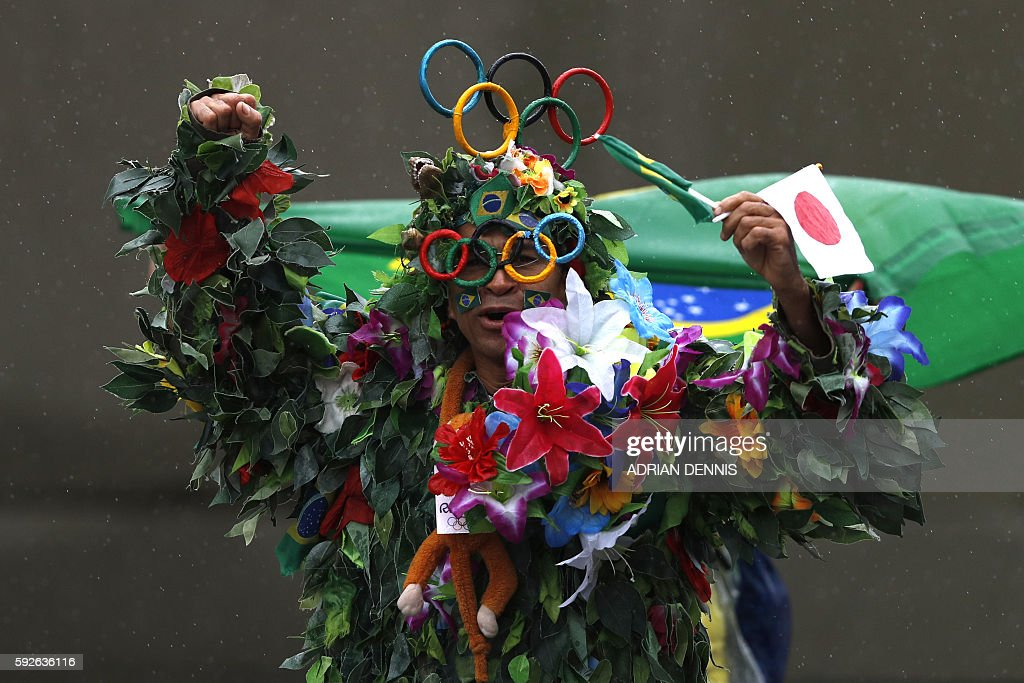 TOPSHOT - A supporter dressed as a tree cheers during the Men's Marathon athletics event at the Rio 2016 Olympic Games in Rio de Janeiro on August 21, 2016. / AFP / Adrian DENNIS