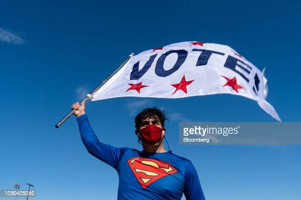 "Supporter dressed as Superman holds a ""VOTE"" flag at a campaign event for Raphael Warnock, U.S. Democratic Senate candidate, in Riverdale, Georgia,..."