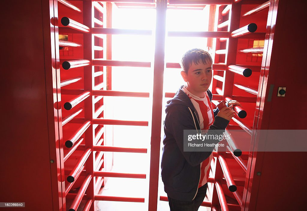 A supporter enters the ground through the turnstiles prior to the Barclays Premier League match between Stoke City and Norwich City at the Britannia Stadium on September 29, 2013 in Stoke on Trent, England.