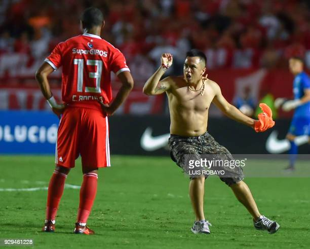 A supporter enters the pitch and shouts to Colombia's America de Cali footballer Juan Angulo during their Copa Sudamericana 2018 football match...