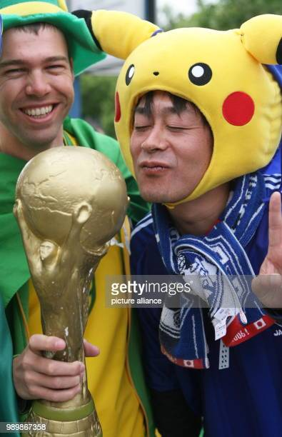 A supporter from Japan kisses a replica of the World Cup shown by a Brazilian supporter prior to the group F match of 2006 FIFA World Cup between...
