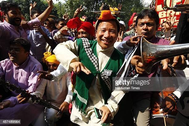 BJP supporter from Northeastern state of Nagaland celebrates following the results of Haryana and Maharashtra state assembly elections at BJP party...
