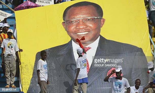A supporter gestures next to a poster of Chad's incumbent president Idriss Deby Itno on April 8 2016 at the Ndjamena stadium during a presidential...